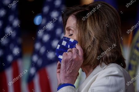 Stock Picture of Speaker of the House Nancy Pelosi, wearing a Donna Lewis face mask, listens as House Majority Whip Jim Clyburn responds to a question on government responses to the COVID-19 coronavirus pandemic in the US Capitol in Washington, DC, USA, 30 April 2020. Speaker Pelosi has named House Majority Whip Jim Clyburn to lead the oversight panel for the 484 billion US dollars relief package that includes hundreds of billions of dollars in funding for small businesses affected by the COVID-19 coronavirus pandemic.
