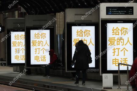 """Pedestrian walks in silhouette through a Chicago Transit Authority bus stop as a COVID-19 public service message in Chinese saying """"Give The People You Love A Call,"""" is projected on screens, in Chicago. The new coronavirus causes mild or moderate symptoms for most people, but for some, especially older adults and people with existing health problems, it can cause more severe illness or death"""