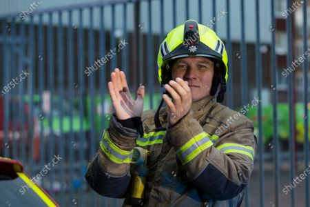 A firefighter from the London Fire Brigade joins staff from the Royal London Hospital during the 'Clap for our Carers' campaign in support of Britain's National Health Service (NHS) in London, Britain, 30 April 2020. 'Clap For Our Carers' is an initiative started by Annemarie Plas where members of the public at 8pm on Thursday give a round of applause for key workers, particularly NHS staff on the frontline treating patients with coronavirus. Britons are now in their fifth week of lockdown due to the ongoing coronavirus COVID-19 pandemic. Countries around the world are taking increased measures to stem the widespread of the SARS-CoV-2 coronavirus which causes the COVID-19 disease.