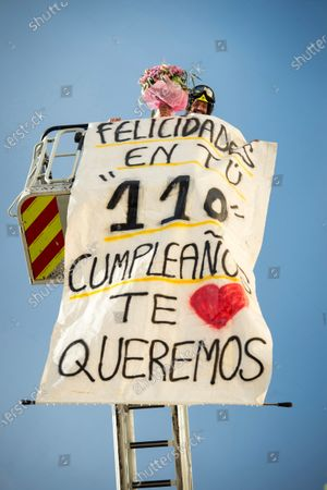 Members of Madrid's firefighting services display a banner reading 'Happy 110th Birthday, we love you' as they deliver a bouquet of flowers to Zofio Cajal (not pictured), the eldest woman in Madrid, to congratulate her on her 110th birthday in Madrid, Spain, 30 April 2020. Spain is in the seventh week of lockdown ordered by the government in an attempt to fight the spread of the pandemic COVID-19 disease caused by the SARS-CoV-2 coronavirus.
