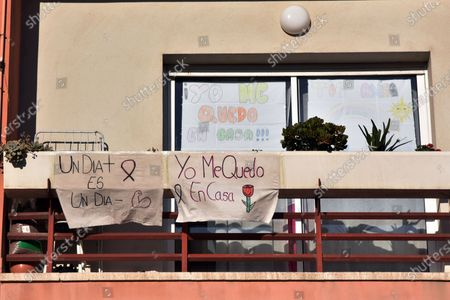 Stock Photo of Hand painted pictures are displayed on a balcony of a house during the coronavirus crisis. People hang hand painted pictures with messages of hope, love and courage, hearts and rainbows on their balconies to encourage their neighbours during the confinement amid coronavirus crisis.