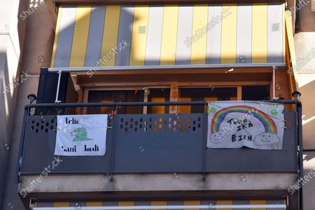 Stock Picture of A banner that says everything will be fine with a colourful rainbow hangs on a balcony of a house during the coronavirus crisis. People hang hand painted pictures with messages of hope, love and courage, hearts and rainbows on their balconies to encourage their neighbours during the confinement amid coronavirus crisis.