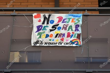 Stock Image of A banner saying Don't stop dreaming, everything will be fine hangs on a balcony of a house during the coronavirus crisis. People hang hand painted pictures with messages of hope, love and courage, hearts and rainbows on their balconies to encourage their neighbours during the confinement amid coronavirus crisis.