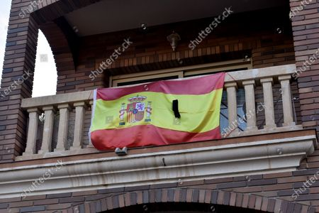 A Spanish flag with black bow in solidarity with the people mourning for their loved ones who died of convirus hangs on a balcony of a house during the coronavirus crisis. People hang hand painted pictures with messages of hope, love and courage, hearts and rainbows on their balconies to encourage their neighbours during the confinement amid coronavirus crisis.