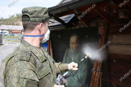 A handout photo made available 30 April 2020 by the press service of the Russian Defense Ministry shows a Russian military specialist disinfecting in the wooden ethno village - tourist resort of Drvengrad (also known as Mecavnik) in Mokra Gora, about 240 km southwest of Belgrade, Serbia, 29 April 2020. Serbian film director Emir Kusturica invited Russian military specialists temporarily stationed in the city of Uzice to visit Drvengrad, a wooden village founded and designed by Kusturica. Russia helps Serbia, its longtime West Balkan ally, to combat the spread of the pandemic COVID-19 disease, which is caused by the SARS-CoV-2 coronavirus.