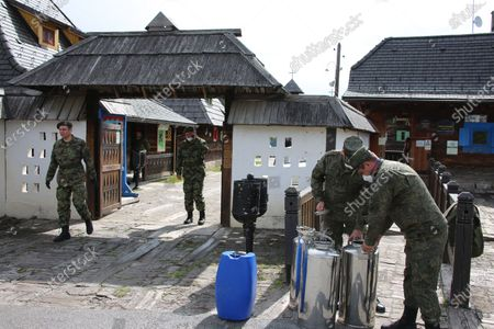 Stock Picture of A handout photo made available 30 April 2020 by the press service of the Russian Defense Ministry shows Russian military specialists disinfecting the wooden ethno village - tourist resort of Drvengrad (also known as Mecavnik) in Mokra Gora, about 240 km southwest of Belgrade, Serbia, 29 April 2020. Serbian film director Emir Kusturica invited Russian military specialists temporarily stationed in the city of Uzice to visit Drvengrad, a wooden village founded and designed by Kusturica. Russia helps Serbia, its longtime West Balkan ally, to combat the spread of the pandemic COVID-19 disease, which is caused by the SARS-CoV-2 coronavirus.