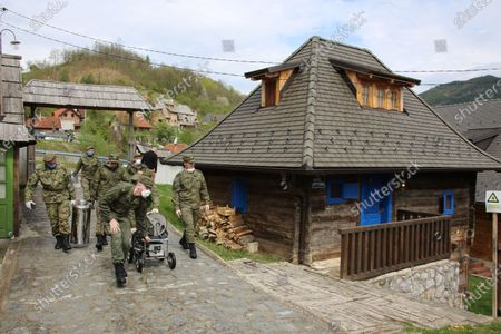A handout photo made available 30 April 2020 by the press service of the Russian Defense Ministry shows Russian military specialists disinfecting the wooden ethno village - tourist resort of Drvengrad (also known as Mecavnik) in Mokra Gora, about 240 km southwest of Belgrade, Serbia, 29 April 2020. Serbian film director Emir Kusturica invited Russian military specialists temporarily stationed in the city of Uzice to visit Drvengrad, a wooden village founded and designed by Kusturica. Russia helps Serbia, its longtime West Balkan ally, to combat the spread of the pandemic COVID-19 disease, which is caused by the SARS-CoV-2 coronavirus.