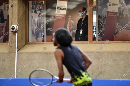 Man wearing a face mask watches from a window as Germany's tennis player Dustin Brown plays during a pro-tennis tournament at a local base tennis academy in Hoehr-Grenzhausen, western Germany, . The professional tennis exhibition in the small village in the Westerwald is a rare exception to the global shutdown of sports during the coronavirus pandemic. Matches are played without line judges and without spectators, and broadcasted by remote cameras worldwide