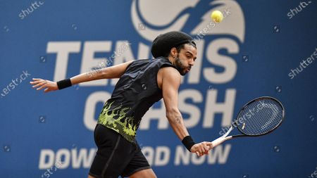 Germany's tennis player Dustin Brown returns the ball during a pro-tennis tournament at a local base tennis academy in Hoehr-Grenzhausen, western Germany, . The professional tennis exhibition in the small village in the Westerwald is a rare exception to the global shutdown of sports during the coronavirus pandemic. Matches are played without line judges and without spectators, and broadcasted by remote cameras worldwide