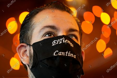 Bartender Julio Gonzalez wears a mask as he waits for the doors to open at El Tiempo Cantina, in Houston. The restaurant reopened their dining room for table service, with limited capacity, Friday. Texas' stay-at-home orders due to the COVID-19 pandemic have expired and Texas Gov. Greg Abbott has eased restrictions on many businesses that have now opened