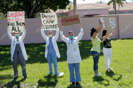 Dr. Franklyn Rocha Cabrero, left, and Dr. Claudia Alvarez, center, and others protest conditions that detainees being held by Immigration and Customs Enforcement face outside of the Broward Transitional Center, during the new coronavirus pandemic, in Pompano Beach, Fla. A Miami federal judge has ordered the release of some detainees from ICE custody at three South Florida detention centers due to conditions related to COVID-19