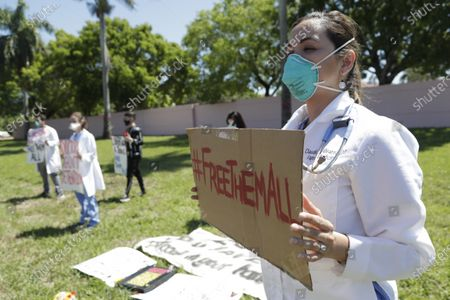 """Stock Picture of Dr. Claudia Alvarez holds a sign saying """"#Free Them All"""" while protesting conditions that detainees being held by Immigration and Customs Enforcement face during the coronavirus pandemic, outside of the Broward Transitional Center in Pompano Beach, Fla. A Miami federal judge has ordered the release of some detainees from ICE custody at three South Florida detention centers due to conditions related to COVID-19"""