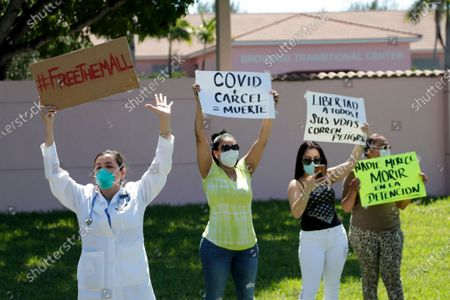 Dr. Claudia Alvarez, left, holds a sign saying Free Them All while protesting conditions that detainees being held by Immigration and Customs Enforcement face outside of the Broward Transitional Center, during the new coronavirus pandemic, in Pompano Beach, Fla. A Miami federal judge has ordered the release of some detainees from ICE custody at three South Florida detention centers due to conditions related to COVID-19