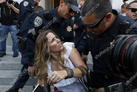 Tara Thornton is detained by California Highway Patrol officers during a demonstration against Gov. Gavin Newsom's stay-at-home orders aimed at slowing the spread of the new coronavirus, at the Capitol in Sacramento, Calif., . Several people were taken into custody during the protest calling for Newsom to end the restrictions and allow people return to work