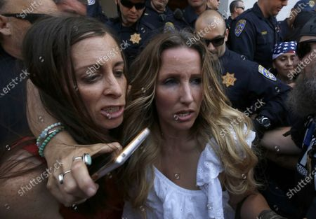 Heidi Munoz Gleisner, left, and Tara Thornton, right, huddle together as they are detained by California Highway Patrol officers during a demonstration against Gov. Gavin Newsom's stay-at-home orders aimed at slowing the spread of the new coronavirus, at the Capitol in Sacramento, Calif., . Several people were taken into custody during the protest calling for Newsom to end the restrictions and allow people return to work
