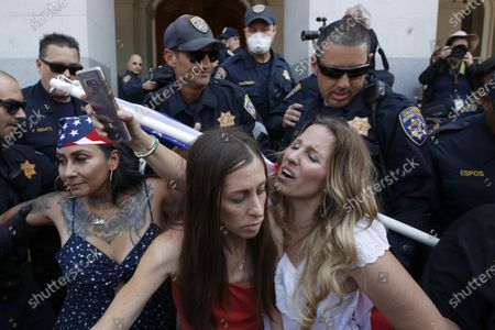 Stock Picture of Heidi Munoz Gleisner, left, and Tara Thornton, right, huddle together as they are detained by California Highway Patrol officers during a demonstration against Gov. Gavin Newsom's stay-at-home orders aimed at slowing the spread of the new coronavirus, at the Capitol in Sacramento, Calif., . Several people were taken into custody during the protest calling for Newsom to end the restrictions and allow people return to work