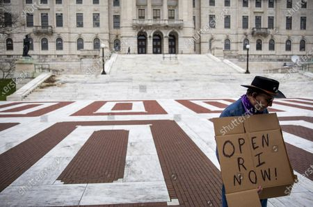 James Dunn stands outside the Statehouse with a handmade sign in favor of reopening the state economy as Gov. Gina Raimondo delivers her daily briefing inside, in Providence, R.I. Raimondo said she still hopes to lift Rhode Island's stay-at-home order in about a week, even though the daily number of new coronavirus cases in the state only appears to have reached a plateau and is not yet on the decline