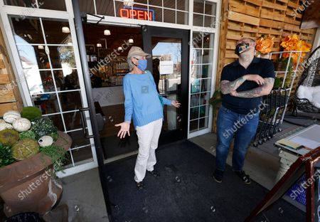 Stock Image of Brenda Erickson, left, of Castle Pines Village, Colo., jokes with Cameron Boman, manager of The Emporium, as retail stores reopened to customers in Douglas County when restrictions put in place to curb the spread of the new coronavirus were rolled back, in Castle Rock, Colo