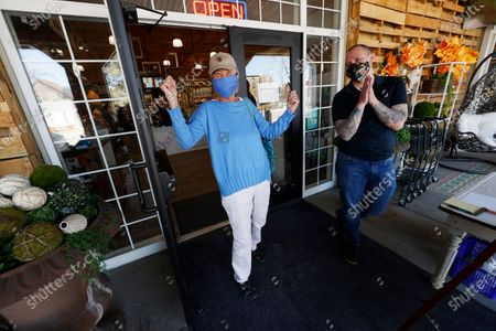 Brenda Erickson of Castle Pines Village, Colo., raises her arms as manager Cameron Boman looks on after Erickson toured The Emporium as retail stores reopened to customers in Douglas County when restrictions put in place to curb the spread of the new coronavirus were rolled back, in Castle Rock, Colo