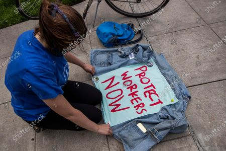 Worker Chelsea Watson from the District of Columbia pins a protest banner on her jack during a rally commemorating May Day, in Washington