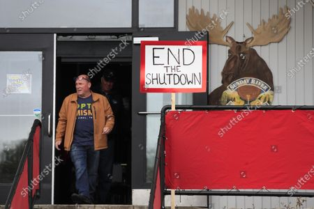Stock Image of Rick Savage, owner of Sunday River Brewing Company, walks out of his restaurant after he defied an executive order that prohibited gathering 10 or more people and opened his establishment during the coronavirus pandemic, in Newry, Maine