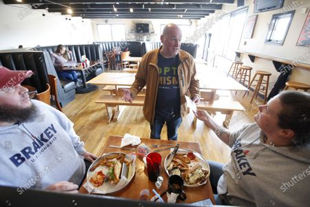 Rick Savage, center, owner of Sunday River Brewing Company, talks with customers Jon and Tiffany Moody after Savage defied an executive order prohibited the gathering of 10 or more people by opening his establishment during the coronavirus pandemic, in Newry, Maine