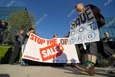 Cory Doctorow, right, walks in front of other protestors in Los Angeles outside the headquarters of the regulatory body for domain names, the Internet Corporation for Assigned Names and Numbers. After widespread opposition, the organization overseeing internet domain names has voted against the $1.1 billion sale of the dot-org online registry to an investment firm. The board of the Los Angeles-based Internet Corporation for Assigned Names and Numbers voted not to allow the sale to Ethos Capital of the website suffix that is widely used by non-profits and community groups