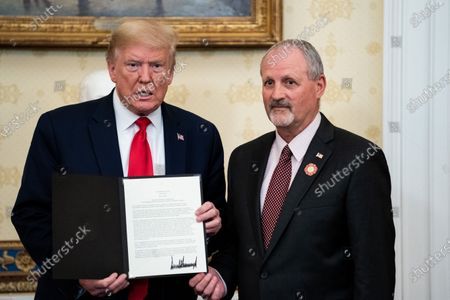 Stock Photo of US President Donald J. Trump presents an award to Frank Siller, founder and president of Tunnel to Towers, during a ceremony honoring volunteers helping others deal with coronavirus at the White House, in Washington, DC, USA, 01 May 2020.