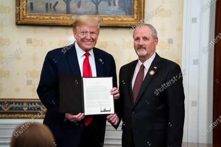 US President Donald J. Trump presents an award to Frank Siller, founder and president of Tunnel to Towers, during a ceremony honoring volunteers helping others deal with coronavirus at the White House, in Washington, DC, USA, 01 May 2020.