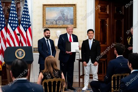 US President Donald J. Trump (C) presents an award to TJ Kim (R), a sophomore at The Landon School, during a ceremony honoring volunteers helping others deal with coronavirus at the White House, in Washington, DC, USA, 01 May 2020.