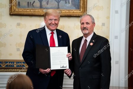 United States President Donald J. Trump presents an award to Frank Siller, founder and president of Tunnel to Towers, during a ceremony at the White House in Washington, DC honoring volunteers helping others deal with coronavirus.