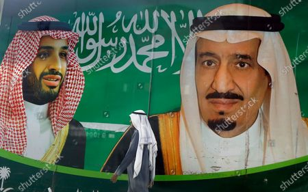 A man walks past a banner showing Saudi King Salman, right, and his Crown Prince Mohammed bin Salman, outside a mall in Jiddah, Saudi Arabia. A beleaguered Saudi Arabia has begun taking modest steps to improve its human rights record as it tries to navigate the coronavirus pandemic and the fallout from plunging oil prices that have rankled the United States. Crown Prince Mohammed bin Salman is pressing ahead with reforms with a wary eye on Iran and is eyeing further steps that he hopes will improve the kingdom's reputation