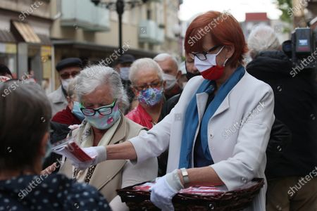 Member of the European Parliament, Elzbieta Rafalska, distributes masks featuring the colors of the Polish national flag  as part of celebrations of the Polish National Flag Day  during the coronavirus pandemic in Gorzow Wielkopolski, western Poland, 02 May 2020. The Polish National Flag Day is celebrated annually on 02 May and is not a national holiday.
