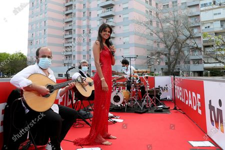 """Portuguese fado singer Cuca Roseta performs at a live concert on the top of a vehicle running through streets in Lisbon, Portugal, on May 1, 2020, amid the COVID-19 pandemic. TO GO WITH """"Feature: Fado concert invigorates Portuguese amid pandemic"""""""