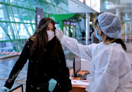 A staff member checks a passenger's temperature at Nursultan Nazarbayev International Airport in Nur-Sultan, Kazakhstan, on May 1, 2020. Kazakhstan has resumed domestic passenger flights between its capital Nur-Sultan and its largest city Almaty, which were suspended on March 30 due to COVID-19. Kazakhstan has reported 3,550 COVID-19 cases and 25 deaths as of Friday. At the end of April, the Kazakh government eased some COVID-19-related restrictions.