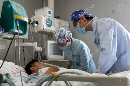 """Nurses Liu Guangyao (1st R) and Qiao Bing (C) take care of a patient at an ICU ward of the Third People's Hospital of Henan in Zhengzhou, central China's Henan Province, April 26, 2020. Liu Guangyao and Qiao Bing are both the hospital's ICU nurses, who are a pair of lovers born in 1990s.     After the COVID-19 pandemic outbreak, both of them filed for aiding the fight against the disease in the hardest-hit Wuhan, capital of central China's Hubei.     On Feb. 2, Liu and Qiao, both included in a provincial Wuhan-aiding medical team, left Henan for the city where they battled the novel coronavirus at local Tongji Hospital for nearly two months.    They originally planned to get engaged on Feb. 9, but obviously they couldn't do it due to the critical work. Unwilling to miss that special day, however, Liu made a simple ring with a clip and proposed marriage to Qiao on that day.     After returning from Wuhan, Liu and Qiao went through a 14-day quarantine, and went back to their nursing work.     """"After those unforgettable experiences in Wuhan, we both gained a deeper insight into our work now and would cherish our life more in the future. We have also planned to get married late this year or early in the next year,"""" said Li."""