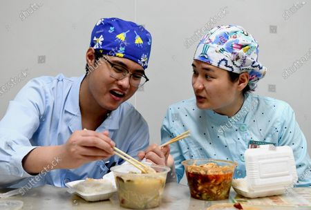 """Nurses Liu Guangyao (L) and Qiao Bing have lunch during work break at the Third People's Hospital of Henan in Zhengzhou, central China's Henan Province, April 26, 2020. Liu Guangyao and Qiao Bing are both the hospital's ICU nurses, who are a pair of lovers born in 1990s.     After the COVID-19 pandemic outbreak, both of them filed for aiding the fight against the disease in the hardest-hit Wuhan, capital of central China's Hubei.     On Feb. 2, Liu and Qiao, both included in a provincial Wuhan-aiding medical team, left Henan for the city where they battled the novel coronavirus at local Tongji Hospital for nearly two months.    They originally planned to get engaged on Feb. 9, but obviously they couldn't do it due to the critical work. Unwilling to miss that special day, however, Liu made a simple ring with a clip and proposed marriage to Qiao on that day.     After returning from Wuhan, Liu and Qiao went through a 14-day quarantine, and went back to their nursing work.     """"After those unforgettable experiences in Wuhan, we both gained a deeper insight into our work now and would cherish our life more in the future. We have also planned to get married late this year or early in the next year,"""" said Li."""
