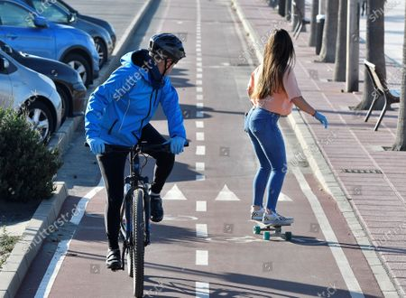 A cyclist looks back at a woman riding a skateboard in the opposite direction on a bike lane in Almeria, southern Spain, 02 May 2020. Starting on 02 May, Spain has begun to loosen some of the strict lockdown measures imposed in a bid to slow down the spread of the pandemic COVID-19 disease caused by the SARS-CoV-2 coronavirus. Adults and the elderly are once again able to leave their homes for a walk or to perform exercise, albeit with restrictions. The former are allowed to exercise or go out for a stroll between 6-10 am and 8-11 pm, while the latter may leave their homes between 10 am-12 pm and 7-8 pm. Children under the age of 14 can go out between 12-7 pm.