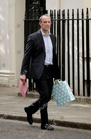 British Foreign Secretary Dominic Raab walks into 10 Downing Street, London, for a coronavirus meeting, carrying a gift after British Prime Minister Boris Johnson's partner Carrie Symonds gave birth on Wednesday to a baby boy named Wilfred, . The highly contagious COVID-19 coronavirus has impacted on nations around the globe, many imposing self isolation and exercising social distancing when people move from their homes