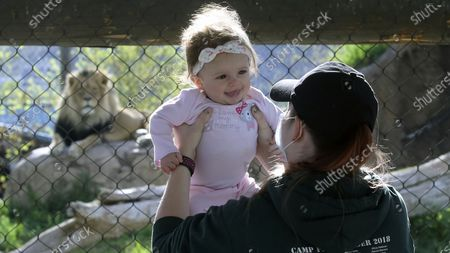 Stock Photo of Holly Stuart holds her daughter Savannah during a visit to Utah's Hogle Zoo, in Salt Lake City. The zoo is one of many Utah businesses reopening Saturday amid the Coronavirus pandemic after multi-week closure. The zoo will restrict the number of guests who enter per day to help with social distancing