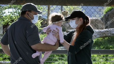 Kevin and Holly Stuart hold their daughter Savannah during a visit to Utah's Hogle Zoo, in Salt Lake City. The zoo is one of many Utah businesses reopening Saturday amid the Coronavirus pandemic after multi-week closure. The zoo will restrict the number of guests who enter per day to help with social distancing