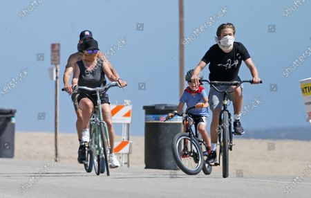 Reese Witherspoon and family wear masks as they ride bikes on the beach during quarantine