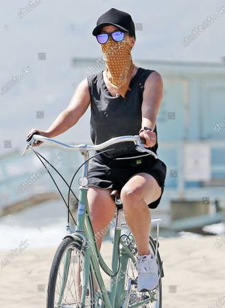 Stock Image of Reese Witherspoon and family wear masks as they ride bikes on the beach during quarantine