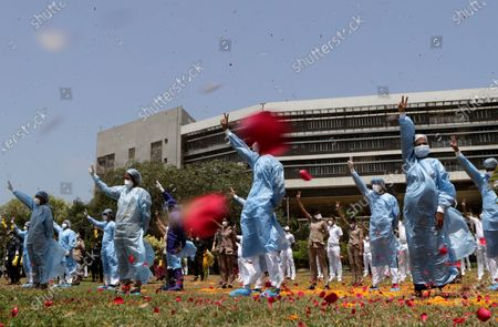 An Indian Air Force helicopter showers flower petals on the staff of INS Ashwini hospital in Mumbai, India, . The event was part the Armed Forces' efforts to thank the workers, including doctors, nurses and police personnel, who have been at the forefront of the country's battle against the COVID-19 pandemic