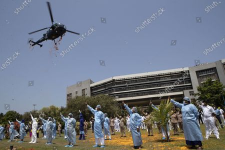 Stock Photo of An Indian Air Force helicopter showers flower petals on the staff of INS Ashwini hospital in Mumbai, India, . The event was part the Armed Forces' efforts to thank the workers, including doctors, nurses and police personnel, who have been at the forefront of the country's battle against the COVID-19 pandemic