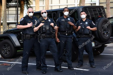 Hallandale Beach police officers wearing protective masks. Firefighters and a Hazmat team on call at a Condominium apartment building on Saturday, May, 2020 in Hallandale Beach, Fla. Stay at home order is still in effect in Broward County do to the Coronavirus pandemic. Many people due to the order, were seen on their balconies and at the windows viewing the rescue teams below.