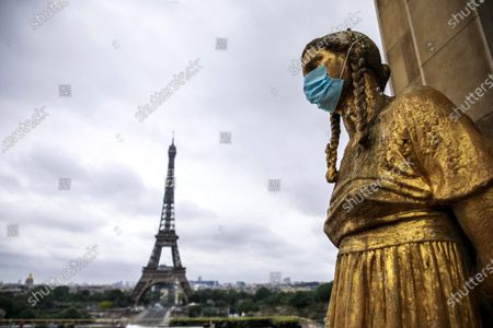 The golden statues of the Trocadero esplanade, in front of the Eiffel Tower, are covered with protective face masks in Paris, France, 03 May 2020. French government plans to decreases containment measures and traffic restrictions taken to stop the widespread of the SARS-CoV-2 coronavirus from 11 May and to make mandatory to wear a protective mask on public transportation.