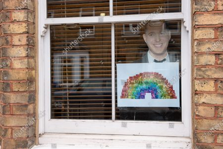Stock Picture of A Michael Buble cut out and rainbow in a house window in Windsor brings a ray of sunshine, hope and positivity during the Coronavirus outbreak