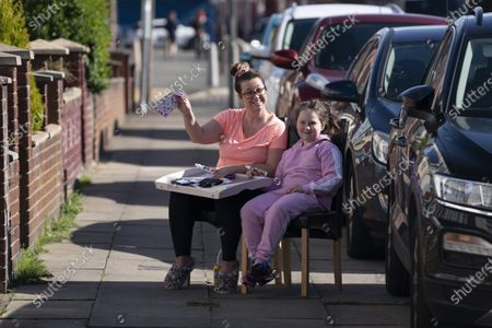Leanne Sargeant with her daughter Disy-Sophia celebrate after a win as they take part in a game of Bingo organised by David Walsh as members of the public find ways to entertain themselves while sticking to government guidelines and observing social distancing in Liverpool, Britain on May 2, 2020.