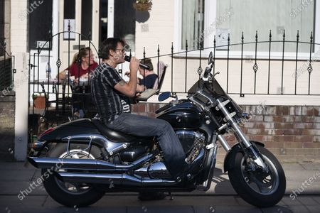 Stock Image of Organiser David Walsh of Dovercliff Road sits on his motorbike whilst reading out the numbers as residents take part in a game of Bingo to entertain themselves while sticking to government guidelines and observing social distancing in Liverpool, Britain on May 2, 2020.